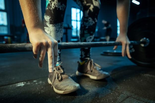 Kaukasische tienermeisje beoefenen in gewichtheffen in de sportschool. vrouwelijke sportieve modeltraining met barbell, ziet er geconcentreerd en zelfverzekerd uit. body building, gezonde levensstijl, beweging en actie concept.