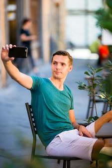 Kaukasische toerist met smartphone die selfie zitting in openluchtkoffie nemen. jonge stedelijke jongen die op vakantie europese stad onderzoekt
