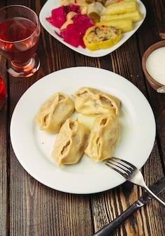 Kaukasische traditionele gerechten, khinkali, dushbere, gurze geserveerd met turshu.