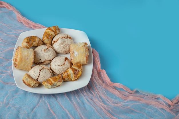 Kaukasische traditionele koekjes met suikerpoeder bovenop op witte keramische plaat.