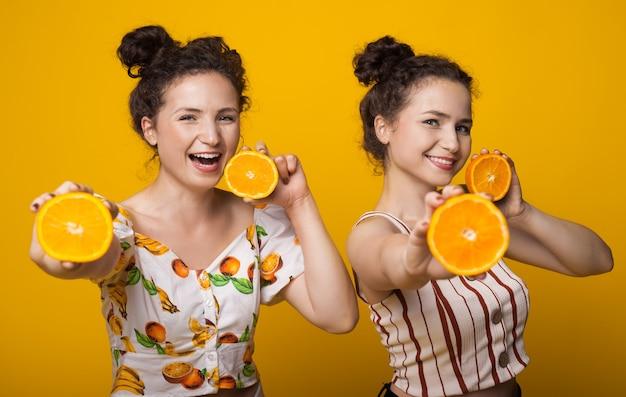 Kaukasische tweeling met krullend haar poseren met sinaasappelen in de hand op een gele muur