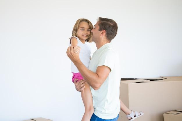 Kaukasische vader die dochter houdt en dichtbij onverpakte dozen danst