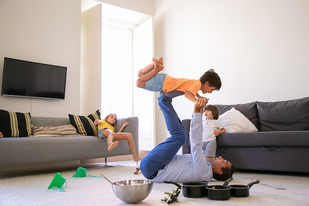 Kaukasische vader die zoon op benen houdt en op tapijt ligt. gelukkig schattige jongen vliegen in de woonkamer met hulp van vader. schattige kinderen spelen samen in de buurt van kom en pannen. jeugd en weekend concept