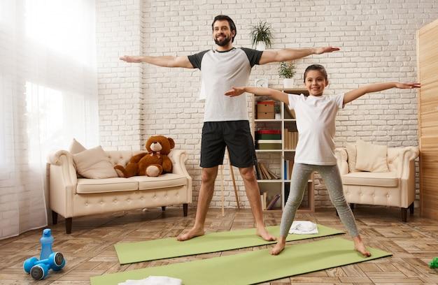 Kaukasische vader en dochter doen stretch oefening thuis