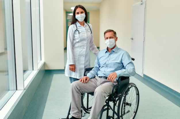 Kaukasische verpleegster die voor een volwassen mannelijke patiënt zorgt die in een rolstoel in het ziekenhuis zit. jonge vrouw en oude man dragen chirurgisch masker ter bescherming tegen covid 19 pandemie.