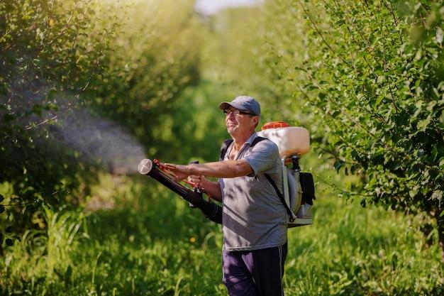 Kaukasische volwassen boer in werkkleding, hoed en met moderne pesticide spray machine op rug spuiten bugs in boomgaard.