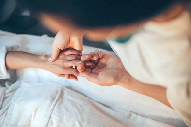 Kaukasische vrouw die bij de kuuroordsalon ligt die een vingermassage bij de hand heeft