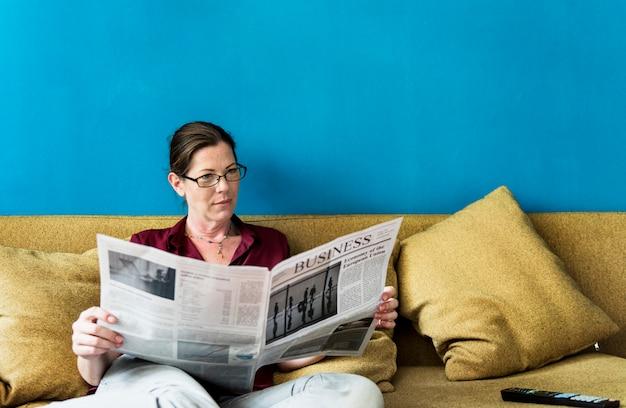 Kaukasische vrouw die de krant leest