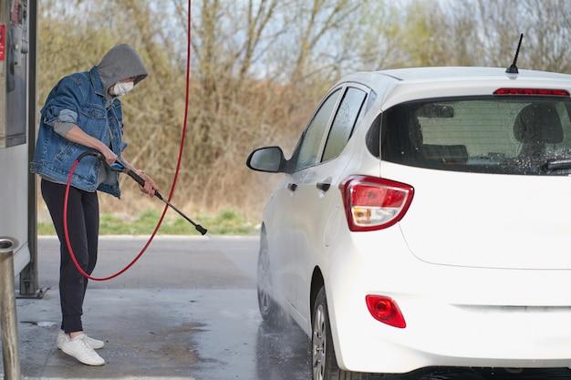 Kaukasische vrouw die haar voertuig op een zelfbedieningsautowasserette wassen