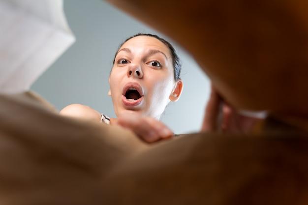 Kaukasische vrouw die in ambachtdocument leveringspakket gluren met verrassingsemotie.