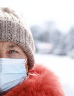 Kaukasische vrouw die medisch masker draagt dat aan de camera bij straat van stad in wintertijd kijkt. veiligheid op openbare plaatsen tijdens uitbraak van coronavirus.