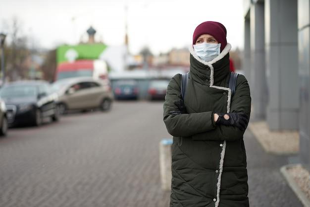 Kaukasische vrouw die medisch masker in openlucht draagt tijdens uitbraak