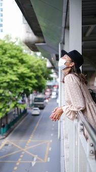 Kaukasische vrouw die op metroovergang in medisch gezichtsmasker loopt terwijl pandemie in de stad van bangkok.