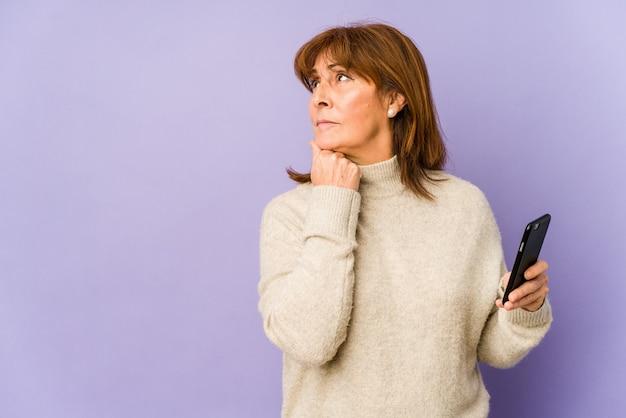 Kaukasische vrouw die van middelbare leeftijd een telefoon houdt die zijdelings met twijfelachtige en sceptische uitdrukking kijkt.