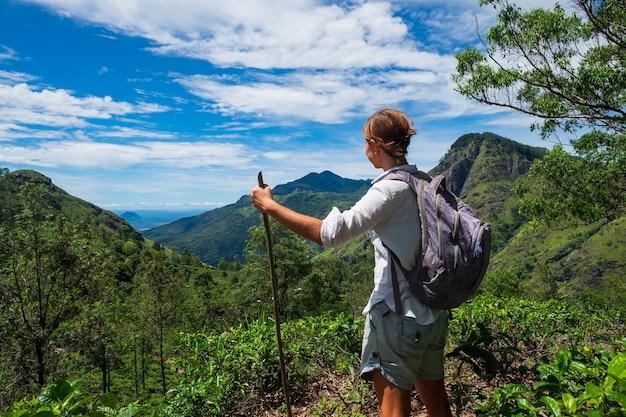 Kaukasische vrouw die zich tussen theestruiken bevindt en op bergen in sri lanka kijkt