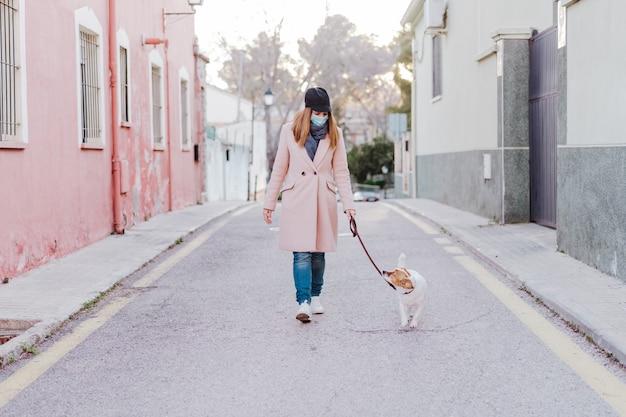 Kaukasische vrouw in de straat die beschermend masker draagt en met haar hond loopt