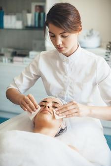 Kaukasische vrouw katoenen schijven toe te passen op het gezicht van de klant tijdens spa-procedures van anti-veroudering