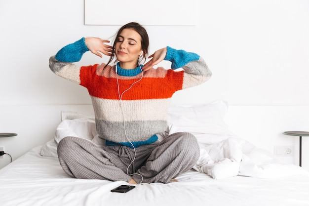 Kaukasische vrouw luisteren naar muziek met smartphone en oortelefoons, zittend in bed thuis