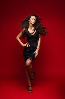 Kaukasische vrouw met aantrekkelijk uiterlijk poseert met veel lucht, foto op rood