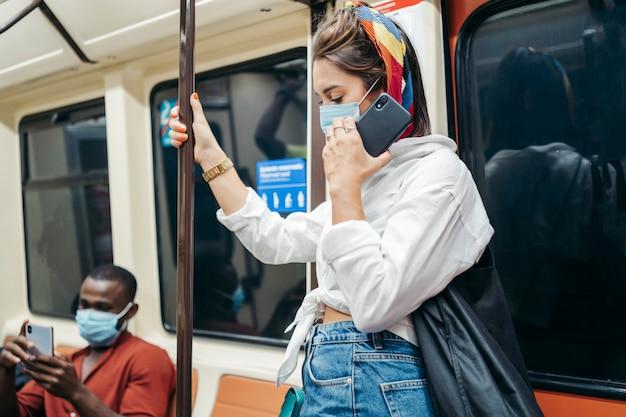 Kaukasische vrouw met chirurgisch masker met smartphone die met de metro reist. ze staat op. er zit een zwarte man achter. zijaanzicht.