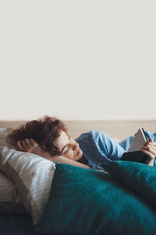 Kaukasische vrouw met gezonde gewoonten en krullend haar die een blauwe pyjama in bed dragen die een boek leest dat op het hoofdkussen ligt