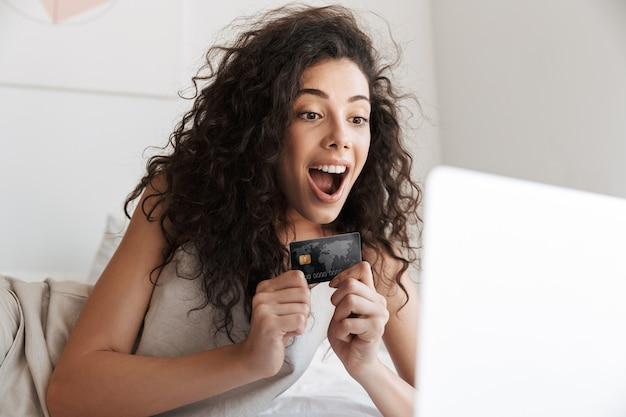 Kaukasische vrouw met lang krullend haar die zijden vrijetijdskleding draagt, liggend in bed met wit linnen in appartement, en online winkelen met laptop en creditcard