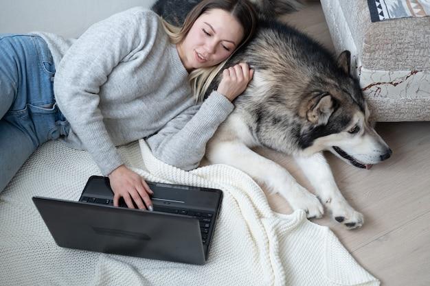 Kaukasische vrouw met malamute-hond die thuis werkt. laptop