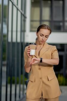Kaukasische vrouw met smartphone die zich tegen straatgebouw bevindt.