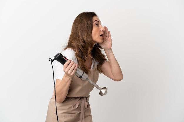 Kaukasische vrouw van middelbare leeftijd die handblender gebruikt die op witte achtergrond wordt geïsoleerd en met wijd open mond naar de zijkant schreeuwt