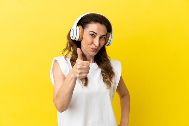 Kaukasische vrouw van middelbare leeftijd geïsoleerd op gele achtergrond luisteren muziek en met duim omhoog