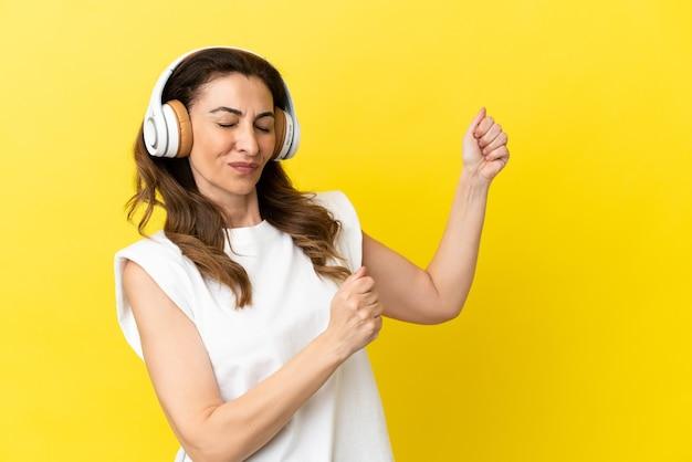 Kaukasische vrouw van middelbare leeftijd geïsoleerd op gele achtergrond muziek luisteren en dansen