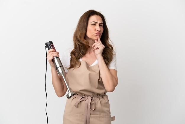 Kaukasische vrouw van middelbare leeftijd met behulp van staafmixer geïsoleerd op een witte achtergrond met twijfels tijdens het opzoeken