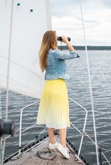 Kaukasische vrouw verrekijker kijken op de zeilboot