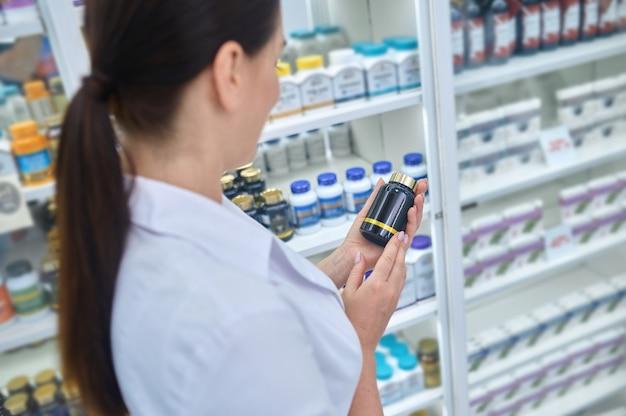 Kaukasische vrouwelijke apotheker die een voedingssupplement onderzoekt