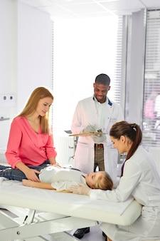 Kaukasische vrouwelijke arts controleert de hartslag van geduldig kind met een stethoscoop, terwijl zijn afrikaanse mannelijke collega haar helpt, in de moderne kliniek