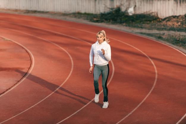 Kaukasische vrouwelijke atleet in sportkleding draait op het stadion met koptelefoon in de oren.