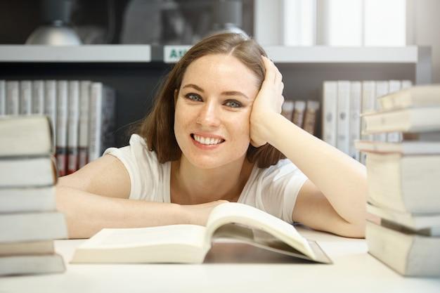 Kaukasische vrouwelijke student met een goed humeur die de vereiste informatie over geschiedenis probeert te vinden, een leerboek bestudeert, in de bibliotheek voor stapels boeken zit, lacht, er blij en tevreden uitziet