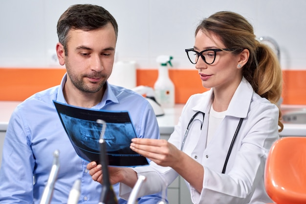 Kaukasische vrouwelijke tandarts die röntgenstraal verklaart