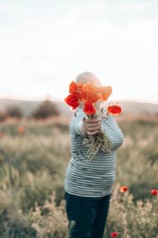 Kaukasische vrouwenhand die een boeket van papaverbloem op weideachtergrond houden bij zonsondergang