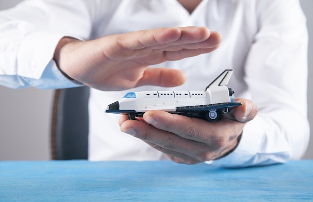 Kaukasische zakenman beschermt speelgoedvliegtuig.