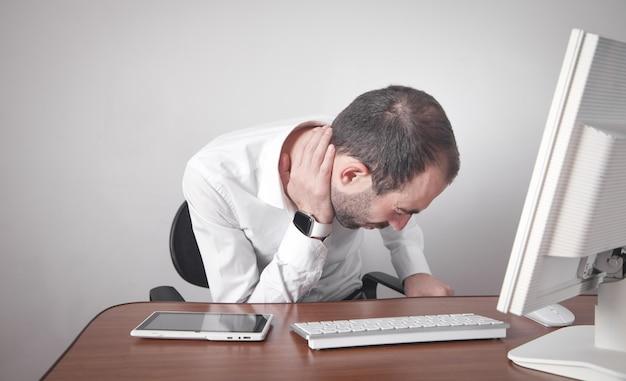 Kaukasische zakenman die aan nekpijn lijden op kantoor.