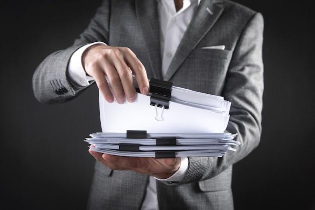 Kaukasische zakenman die documenten op kantoor houdt.