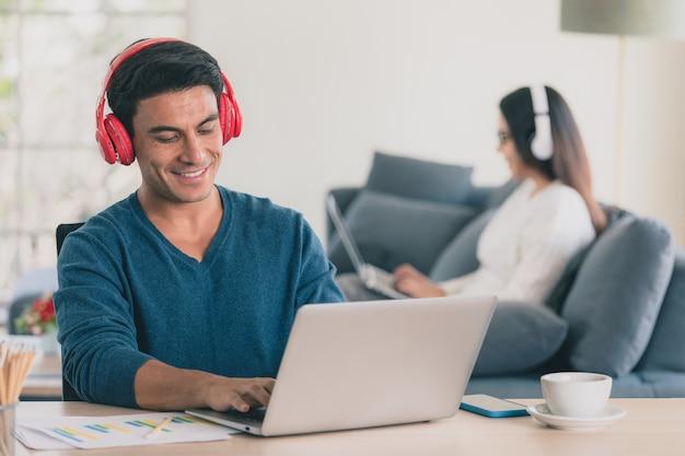 Kaukasische zakenman en aziatische zakenvrouw dragen casual kleding zitten samen in de woonkamer en werken op laptop notebook computer wit op koptelefoon. idee voor modern thuiswerken.