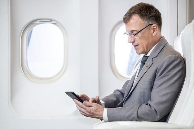 Kaukasische zakenman passagier van vliegtuig zittend in comfortabele stoel werken met slimme telefoon