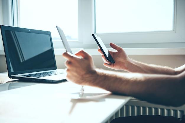 Kaukasische zakenman werkt met een laptop terwijl hij een telefoon vasthoudt aan het bureau bij het raam