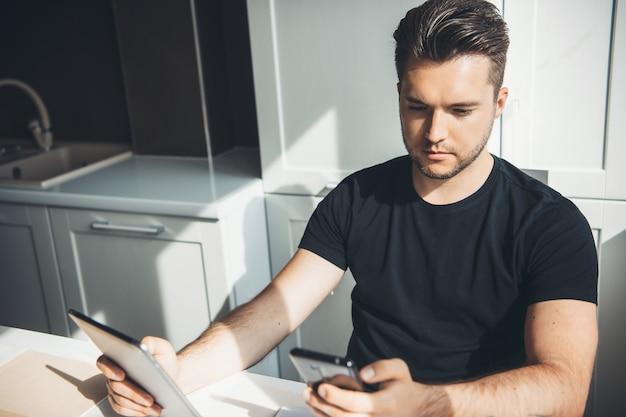 Kaukasische zakenman werkt op afstand thuis met behulp van een telefoon en digitale tablet poseren in de keuken