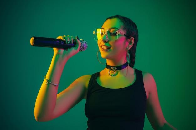 Kaukasische zangeres portret geïsoleerd op groene muur in neonlicht. mooi vrouwelijk model in zwarte slijtage met microfoon. concept van menselijke emoties, gezichtsuitdrukking, advertentie, muziek, kunst.