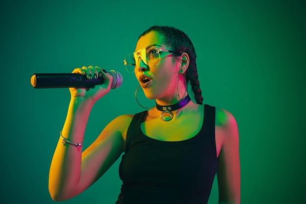 Kaukasische zangeres portret geïsoleerd op groene muur in neonlicht. mooi vrouwelijk model in zwarte slijtage met microfoon.