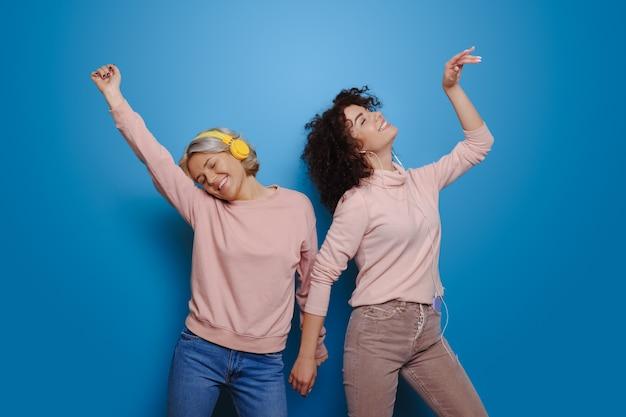 Kaukasische zusters vol emoties luisteren naar muziek met koptelefoon op een blauwe muur