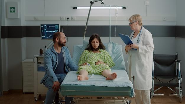 Kaukasische zwangere persoon krijgt advies van arts